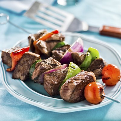 A plate stacked with healthy meat and vegetable skewers.