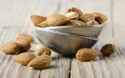 Almonds in a bowl on a wood table.