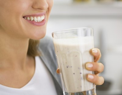 A woman drinks a smoothie.
