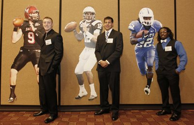 College Football Players next to life-size posters of themselves