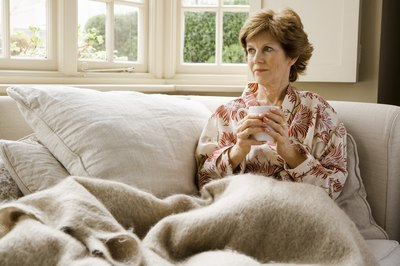 woman on couch with blanket and warm tea