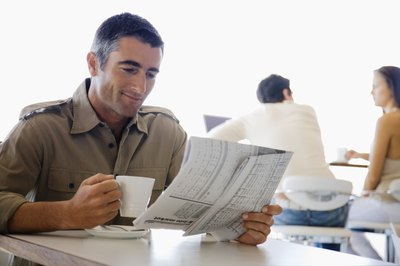 Man reading paper in coffee shop