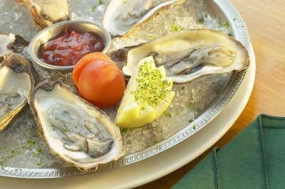 A raw  oyster platter with dipping sauce and garnishes.