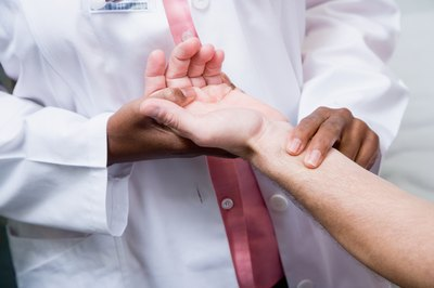 A doctor examining the arms.