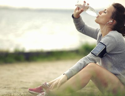 Woman drinks water after exercising