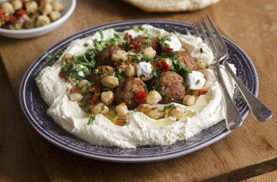A plate of hummus with falafel and chickpeas.