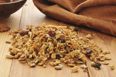 A pile of organic granola on a wood table.
