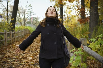 A woman inhaling a deep breath of fresh air on a walking trail in the woods on a fall day.