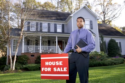 A young real estate agent standing next to a house for sale sign.