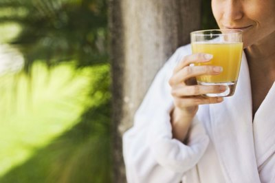 A woman drinks a glass of orange juice.