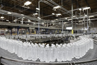 Factory line of water bottles on conveyor belt.