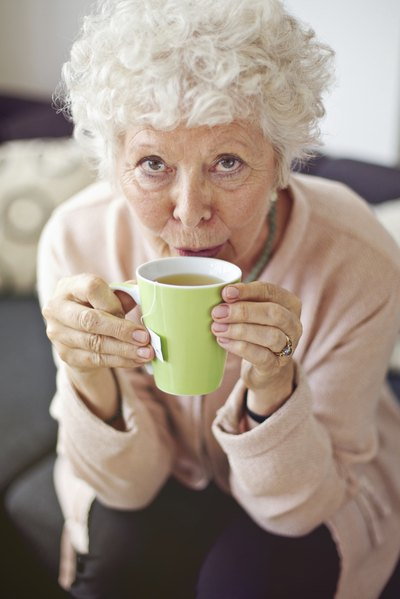 A woman sips a cup of hot tea.
