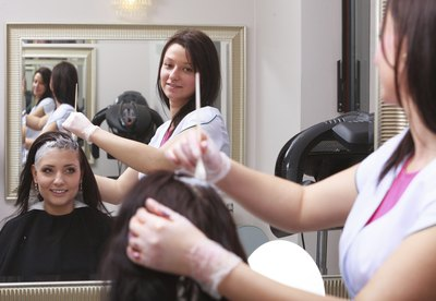 Woman having hair dyed in salon