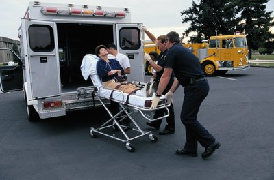 woman getting wheeled into ambulance