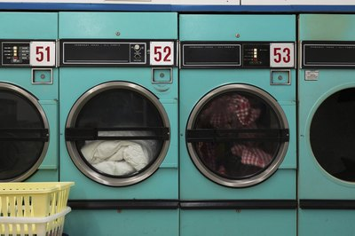 A laundromat with laundry in the washers.