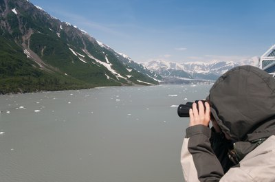 A man examines the Alaskan landscape through binoculars.