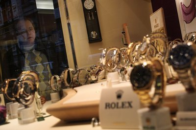 Man looking at Rolex watch display from shop window