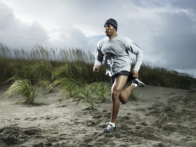 Muscular man running on the beach