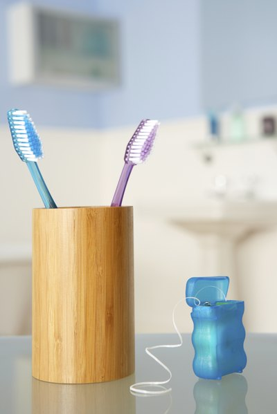 A close-up of dental floss next to a toothbrush holder.