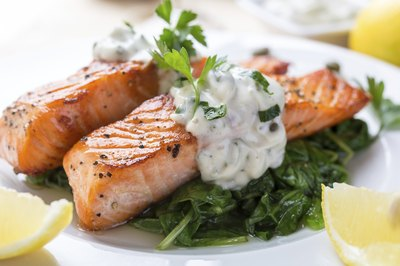 A plate of grilled salmon with a cream sauce on sauted spinach.