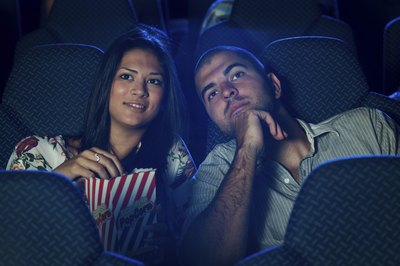 A couple eating popcorn and watching a scary movie at the theater.