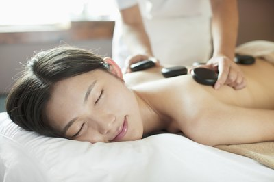 A young woman is at a spa getting a massage.