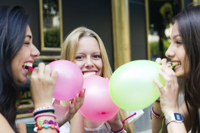 Girls blowing up balloons at birthday party.