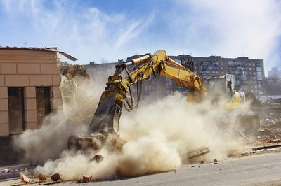 An excavator destroys a builidings wall.