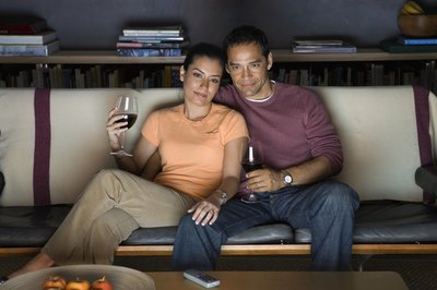 A couple watching tv and drinking wine