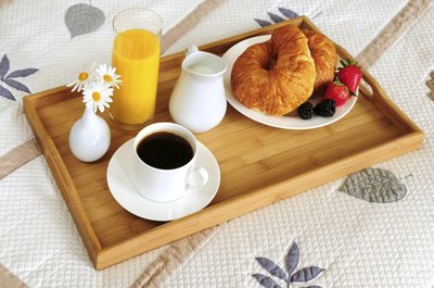 A tray with coffee and breakfast on the edge of a bed.