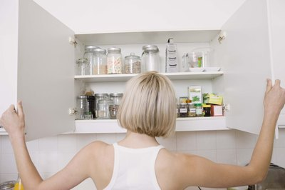 Woman opens kitchen cabinets with both hands.