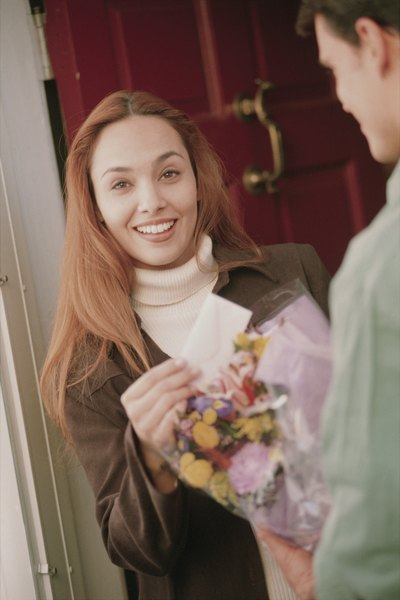 Woman receiving flowers from delivery man