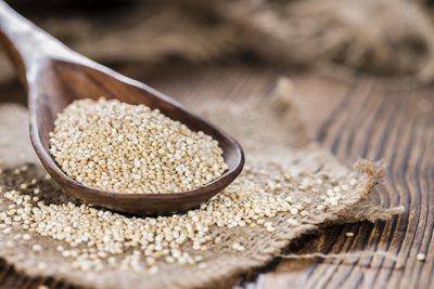 Wooden spoonful of dry quinoa.