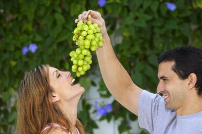 A man feeding his girlfriend some grapes.