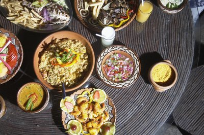 A birds eye view of Honduran dishes served with a bowl of chimole on a rustic table.