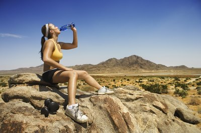 A female hiker drinks from a water bottle on a mountain trail