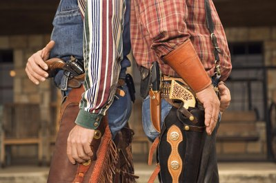 Two men dressed as cowboys standing back to back