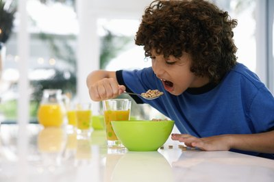 A boy eating a spoonful of breakfast cereal.
