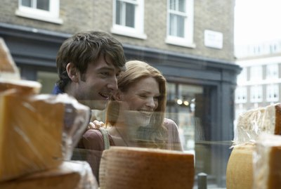 A couple looks in the window of a cheese shop.