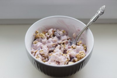 A bowl of flavored fruit yogurt with crunchy granola.