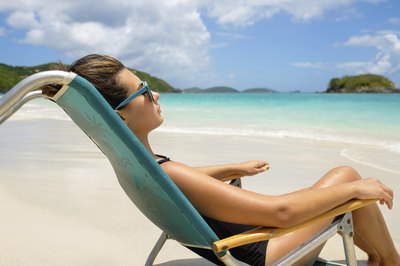 A young woman reclines in a lounge chair on the beach.