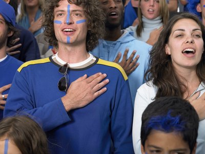 A young couple stand together while singing the national anthem, each has a hand placed over the heart