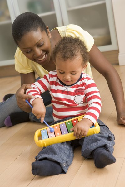 Mother and baby playing with toy xylophone