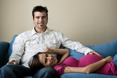 pregnant woman lying on couch with husband