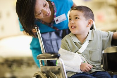 A boy is transported in a wheelchair by a physician.