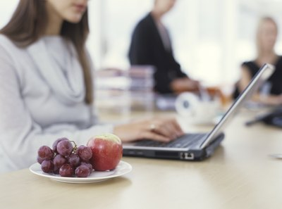 Woman sitting with fruit snack next to her on desk