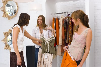 employee interacting with customers at clothing store