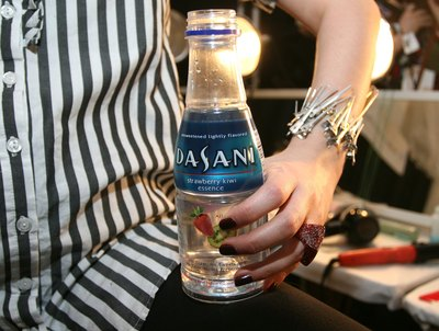 A model holds a bottle of Dasani water