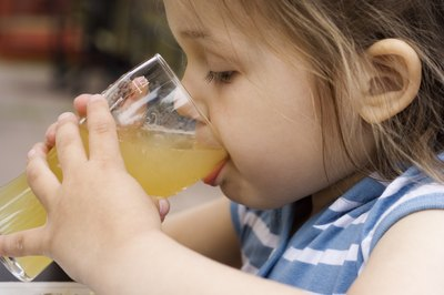 A little girl drinking a glass of apple juice at an outside table.