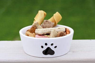 Biscuits and bones in a dog food dish.